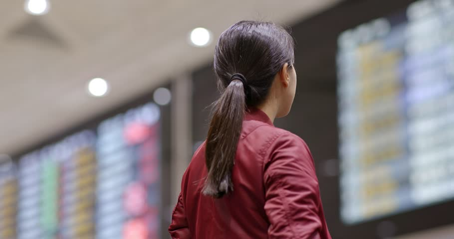 Young woman look at the flight number in the airport | Shutterstock HD Video #1021685257