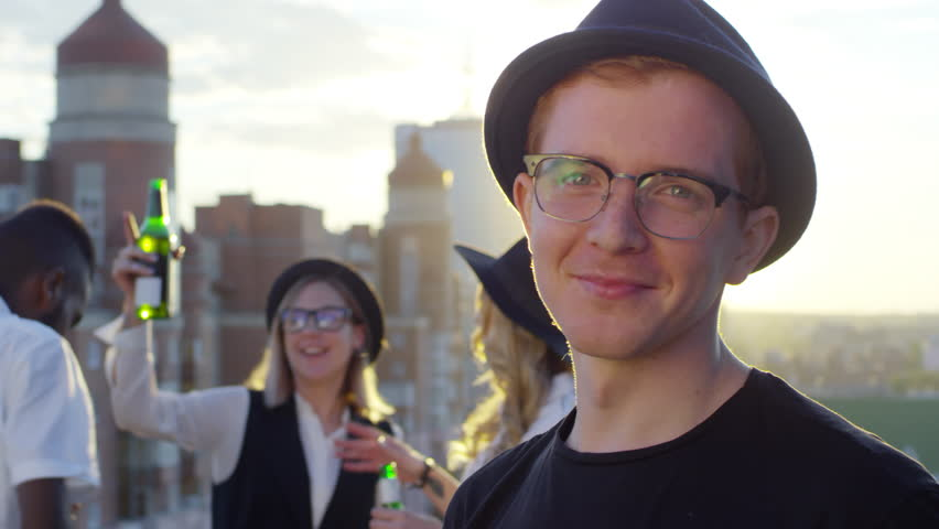 Portrait of young redhead man wearing glasses and fedora hat looking at camera and smiling while his multiracial friends dancing with beers in the background at party on city rooftop at sunset