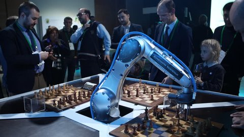ST. PETERSBURG, RUSSIA - DECEMBER 27, 2018: Robot playing chess with men in Exhibition Hall Manege during World Rapid and Blitz Chess Championships. The robot simultaneously plays on 3 chess boards