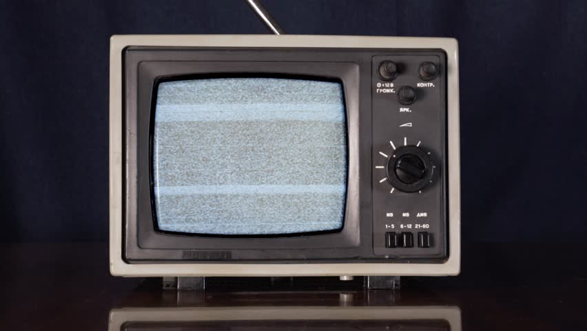 Old vintage TV switching on and off. Zoom in shot of small 70s style television showing white noise on vintage table display. #1021732327