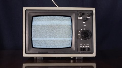 Old vintage TV switching on and off. Zoom in shot of small 70s style television showing white noise on vintage table display.