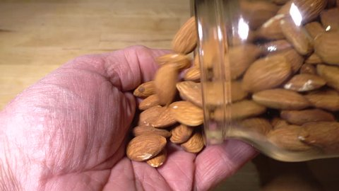 Slow motion close POV overhead shot of a man's hands holding a glass jar and shaking almond nuts from it into the palm of his hand.