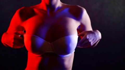 Close-up of a sexy woman putting on a strapless bra in a studio, red light falls on her body from left.