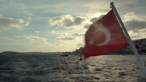 Red Turkish Symbol Flag On Wind.Turkish Flag On Side Of Boat.Banner On Boat Ship In The Wind in Istanbul at Sunset.Vivid Red Turkish Flag Flutter On Wind Against, Stern Of Ferry Boat.Red Flag On Boat.
