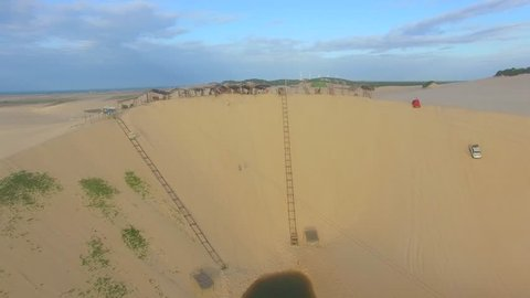 Aerial view of a woman in zipline at sand dunes and two buggies, typical cars, in Canoa Quebrada, in coastline of Ceará, Brazil