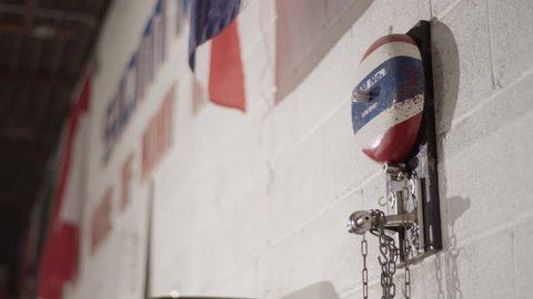 Boxing bell on a wall with flags waving in the background in Muay Thai boxing gym, medium close