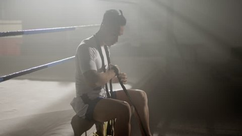 Muay Thai fighter puts on hand wraps while sitting on the edge of a boxing ring in a musty boxing gym, camera rotates around from side to front