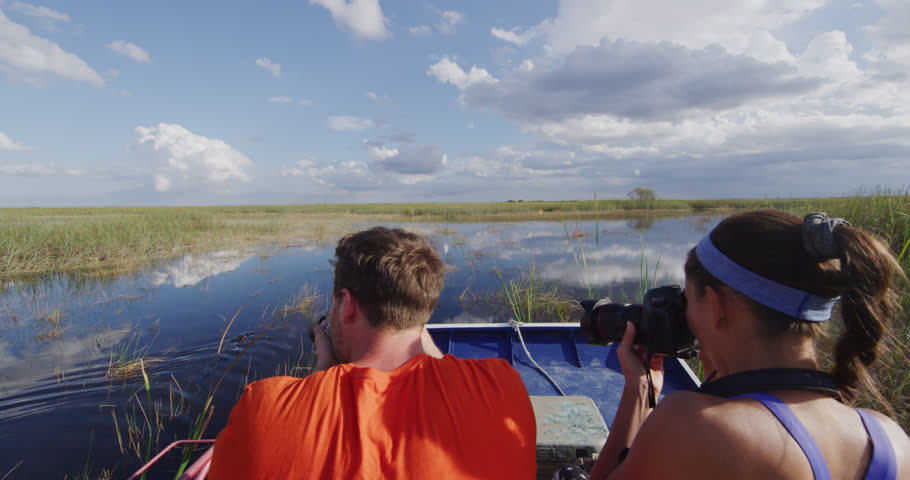 Everglades Airboat tour and alligator - tourists taking picture of alligators on ecotourism travel vacation in Everglades Florida. Airboat tours are a famous tourist activity in the Everglades.