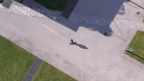 Aerial - Top view of adult businessman going to work on electric scooter