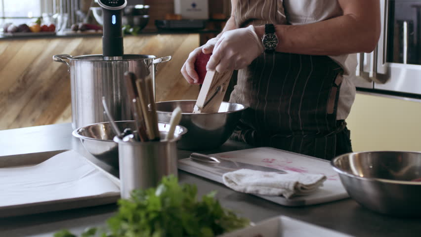 Professional chef grating beets with a mandolin into a bowl while other chefs are working in interior kitchen with soft day lighting. Medium close up to Wide shot on 4k RED camera on a gimbal.