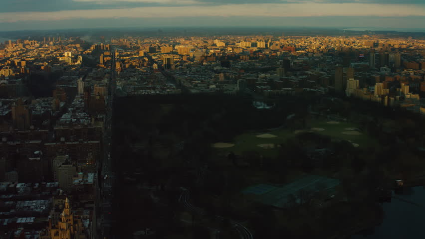 Aerial view of Central Park and buildings and skyscrapers in Manhattan, New York City, during sunset with darker lighting. Shot on 4k RED camera on helicopter.