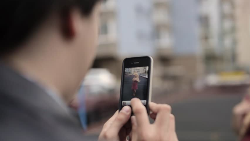 Young girl taking photots on mobile phone of her boyfriend having fun at the street. | Shutterstock HD Video #1022001787