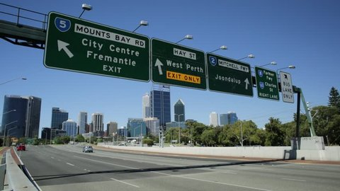 Perth, Western Australia - Jan 3, 2018: Perth highway road sign of Fremantle City Center, West Perth, Jondalup, Farmer Fwy and Charles St in Perth Downtown near John Oldham Park. Traffic urban scene.