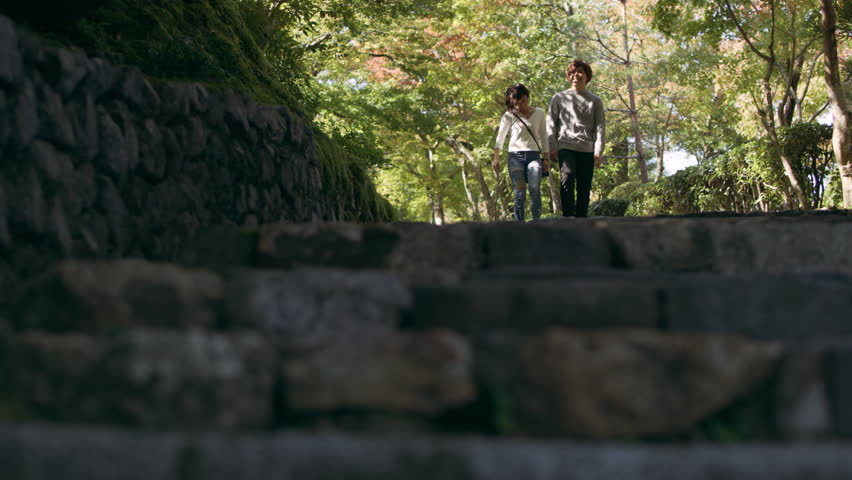 Young couple walking down a stone pathway towards steps under a shaded forest in Kyoto, Japan with soft natural lighting. Medium shot on 4k