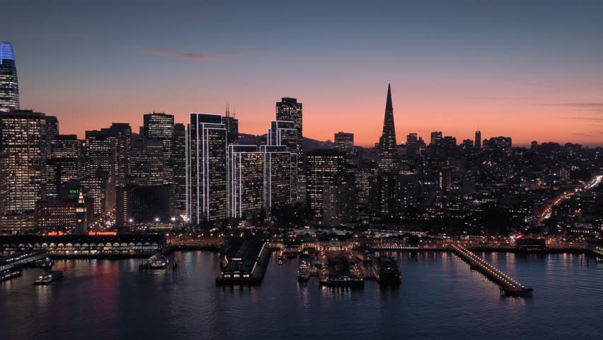 Aerial Drone Of The San Francisco City Skyline, Ferry Terminal and ferries at night. #1022065087