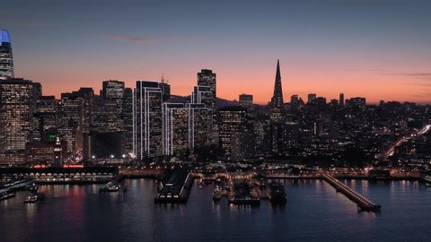 Aerial Drone Of The San Francisco City Skyline, Ferry Terminal and ferries at night.