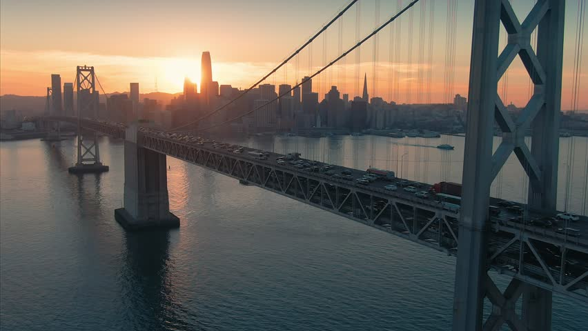 Aerial: The San Francisco City Skyline And Bay Bridge at Sunset.