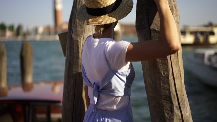 Slow motion, back view of young woman in trendy hat and blue sundress walking on wooden pier in Venezia city enjoying leisure time for travelling around Italy. Carefree female tourist, romantic mood   Shutterstock HD Video #1022093467