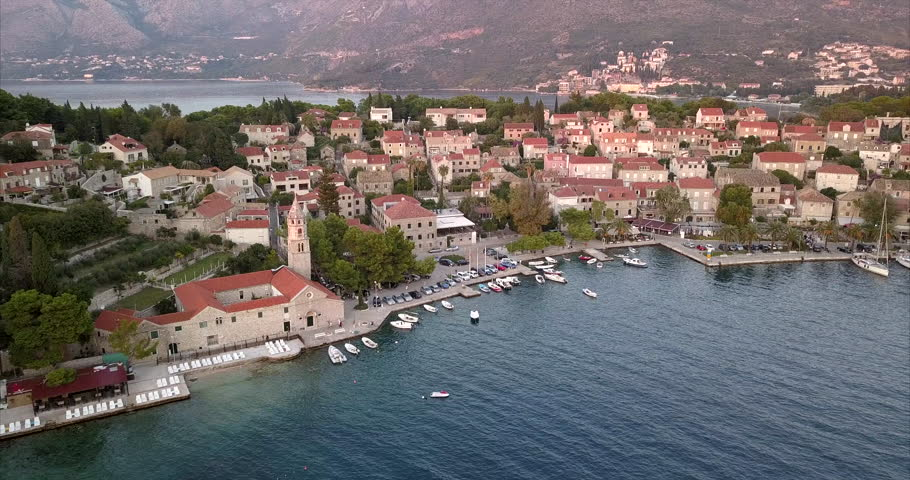 Panning aerial shot with close view of small Croatian village on sea front.