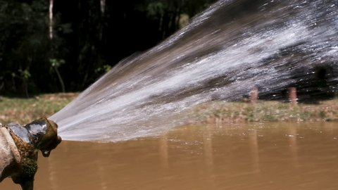 Irrigation hose spraying water into an aquaculture pond