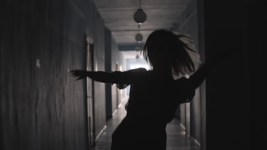 Silhouette of woman in tulle dress dancing and spinning around while going along hallway | Shutterstock HD Video #1022144737