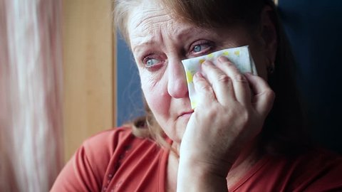 Elderly woman crying wiping her tears with a handkerchief