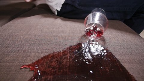 A glass of wine falls on the sofa and spills wine.