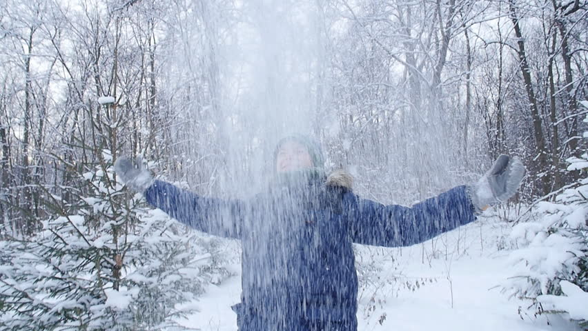 Teen boy throws snow in the winter forest. Active lifestyle, winter activity, outdoor winter games concept