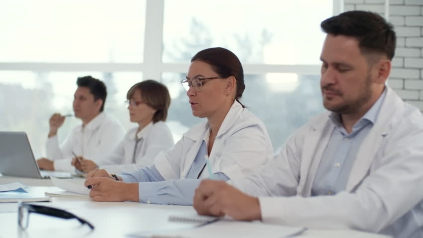 Professional female practitioners in lab coats sitting at desk with male colleagues and asking questions and discussing something with teacher during health seminar | Shutterstock HD Video #1022211487