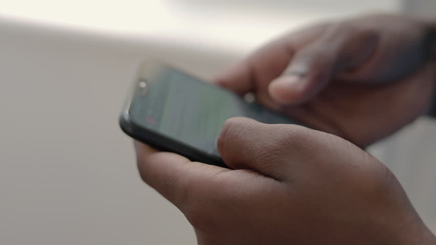 Close up shot of african american student using smartphone. Male hands holding modern phone. Technology concept | Shutterstock HD Video #1022224567