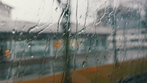 Close-up shot of rain drops and streaks on the window od moving bus by the city street in deep autumn
