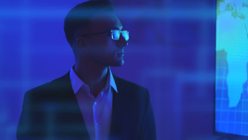 The male in glasses standing near a big screen on hologram background