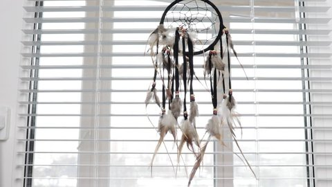 Dream protection amulet dreamcatcher of bird feathers hanging on the window with blinds in the morning, serene dreams talisman.