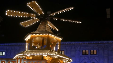 Christmas village market in the imperial palace of residence in Munich, Germany. Part of Antique Christmas mill in the lights, in which there are wooden figures depicting Christmas