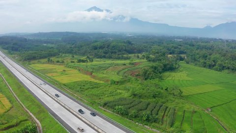 Beautiful aerial scenery of Trans-Java Toll Road with green rice fields and mountain view at Central Java, Indonesia. Shot in 4k resolution