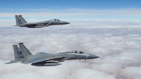 CIRCA 2018 - American F-15 fighter jets fly in formation high above the clouds.