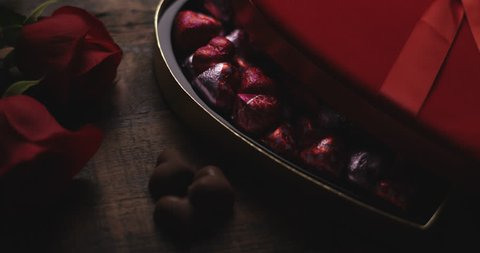 Heart shaped box of chocolates in wrappers on wooden table with roses. Light slowly fades up.