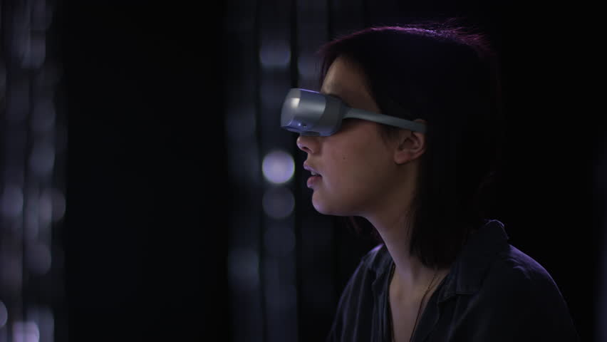 Cute young woman with VR goggles is spectating her virtual surroundings curiously | Shutterstock HD Video #1022489737