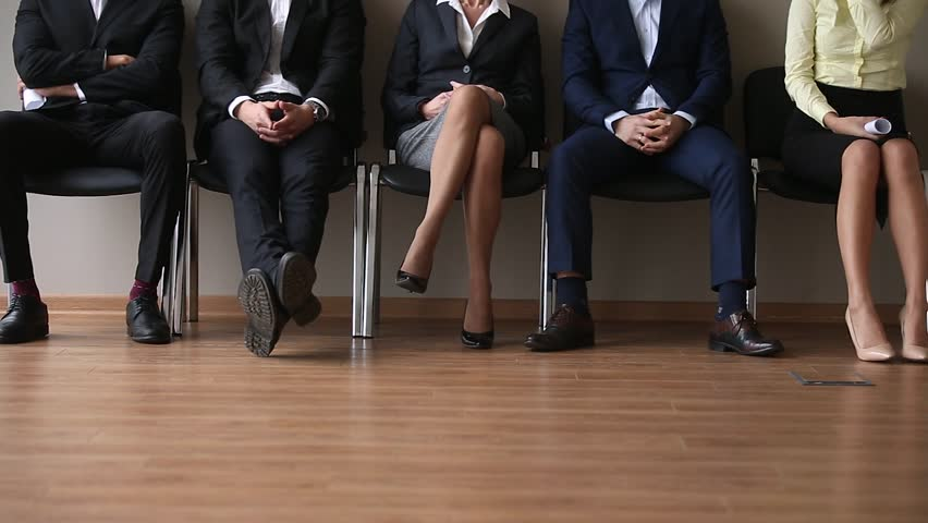 Jobless business people applicants group sitting in chairs in queue line row waiting for their turn company job interview, human resources, recruiting and employment concept, staff legs close up view