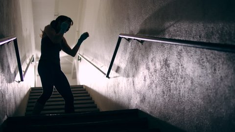 A muscular female fighter shadow boxes in a dark stairwell. She turns towards the camera and shakes out her muscles.