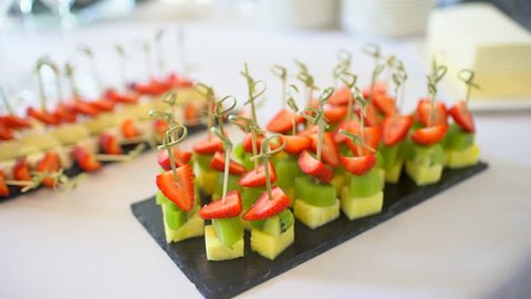 Beautifully decorated catering food banquet table with different food snacks and appetizers canape on corporate birthday party event or wedding celebration. Banquet, Buffet, cheese, kiwi, strawberry