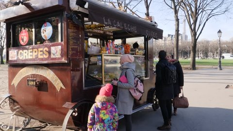 PARIS, FRANCE - DEC 13, 2018: People buy street food point kiosk with coffee and snacks