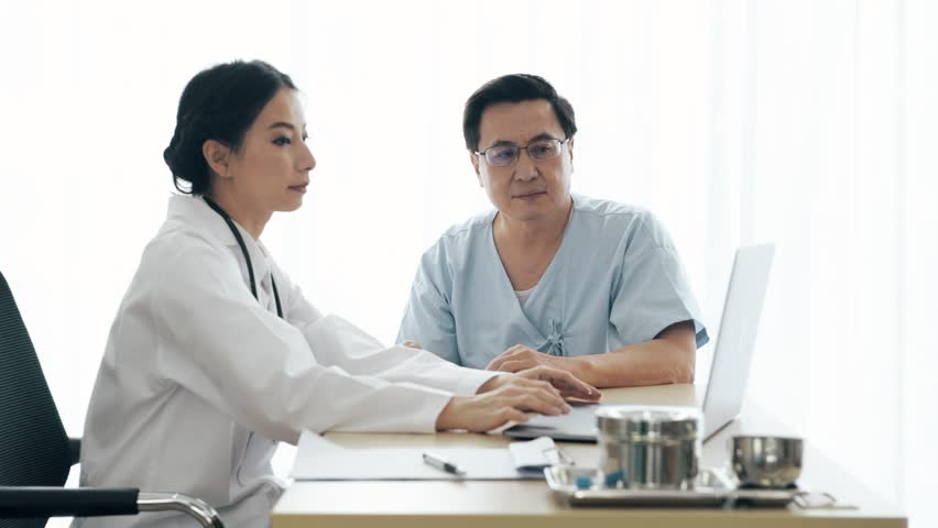 Doctor with patient. Young female medical doctor talking to a senior patient at hospital. Sharing medical test result via computer. Senior care medical and insurance concept. | Shutterstock HD Video #1022583397