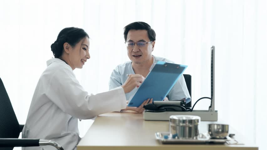 Doctor with patient. Young female medical doctor talking to a senior patient at hospital. Showing her notes. Senior care medical and insurance concept. | Shutterstock HD Video #1022583427