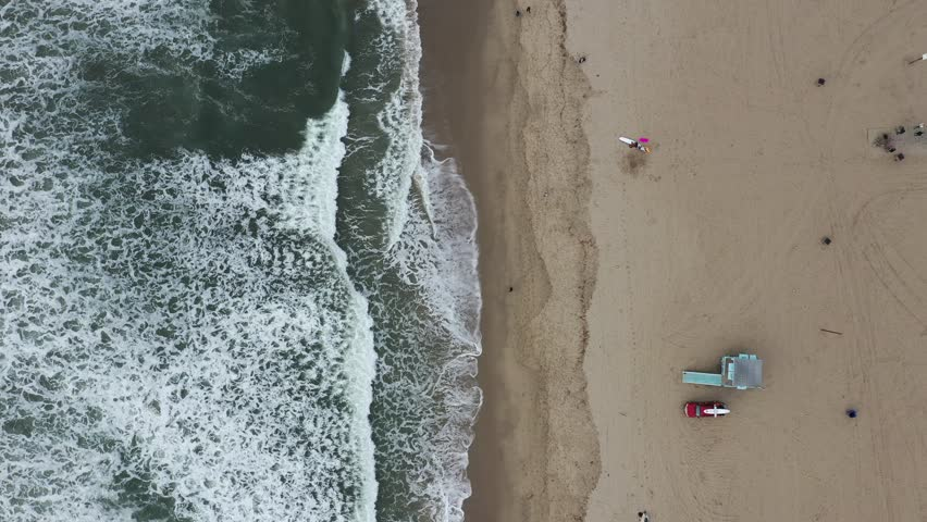 Arial view of waves on a coastline with people at the beach | Shutterstock HD Video #1022586427