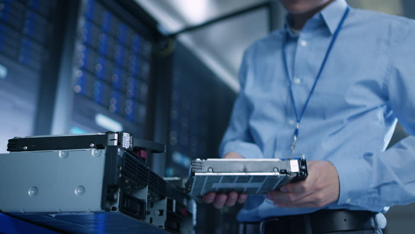 In the Data Center: IT Engineer Installs New HDD Hard Drive and Other Hardware into Server Rack Equipment. IT Specialist Doing Maintenance, Running Diagnostics and Updating Hardware. Low Angle. | Shutterstock HD Video #1022590687