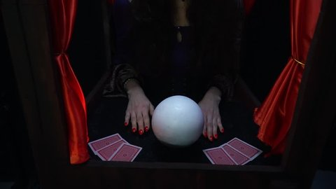 Mystical fortune teller with heavy makeup and red nails, conjuring on the crystal ball