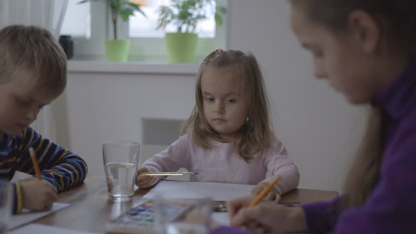 Group of cute children from one family is painting on the paper sitting together #1022626417