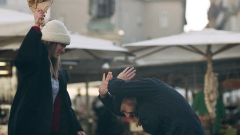 Angry Italian woman taking a bouquet of flowers and hitting a man with them furiously in front of a busy market in Rome with soft natural light. Medium shot on 4k RED camera.