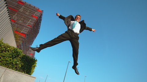 SLOW MOTION LOW ANGLE: Happy corporate professional jumps off the ledge and high into the air. Carefree young man jumping high in air with arms outstretched while celebrating his first job promotion.